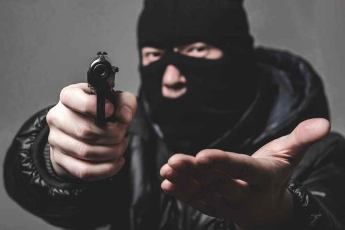 Le malfaiteur vêtu de noir et cagoulé  est entré dans le bar-tabac en exhibant une arme de poing - Illustration © iStock