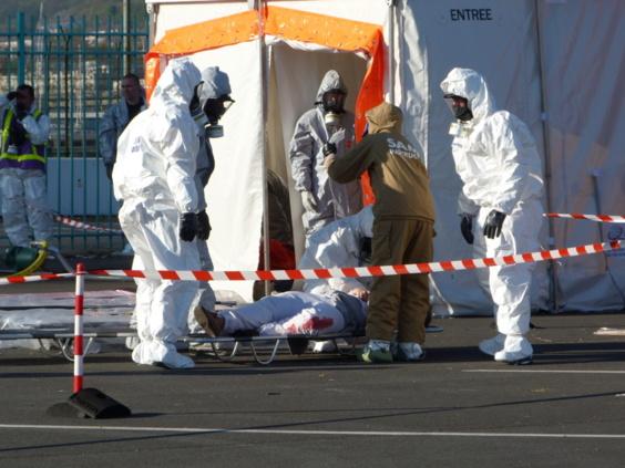 Explosion d'une bombe chimique à bord d'un navire : les secours vêtus d'une combinaison anti-bactériologique portent secours aux victimes