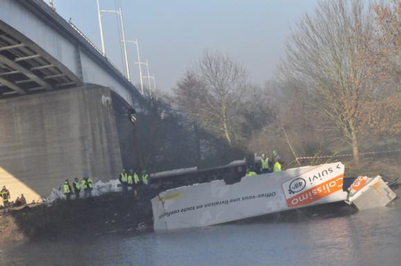 Le poids lourd chargé de colis postaux, qui venait de Rouen, traversait le pont de la Seine avant Pont de l'Arche lorsqu'il a glissé sur la route verglacée. Il s'est déporté sur la gauche et a défoncé le parapet, chutant en contrebas (@Infonormandie)