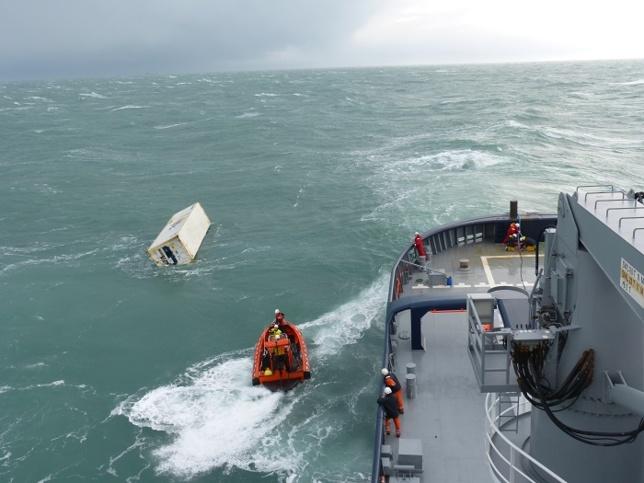 Un conteneur flottant en mer pris en charge par un remorqueur de la Marine