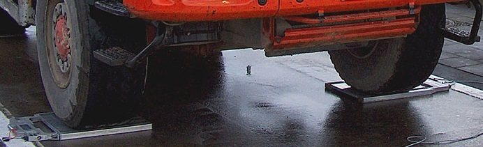 Les contrôles de pesées se font à l'aide de balances portatives glissées sous chaque essieu (Photo d'illustration)