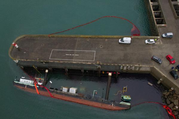 Comme on peut le voir sur cette photo aérienne prise ce lundi matin à bord de l'hélicoptère EC225, un barrage flottant de 300 mètres a été mis en place autour de la barge couchée et du ponton (Photo B.Planchais/Marine nationale)