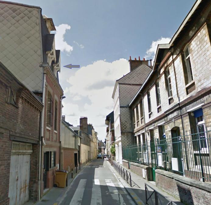 Le logement situé sous les combles (flèche) de ce petit immeuble en briques rouges de la rue Saint-André était complètement embrasé à l'arrivée des secours (Photo d'illustration)