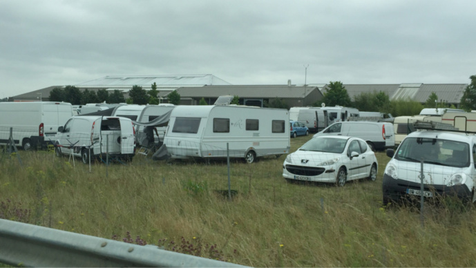 Plus de 180 caravanes et autant de véhicules sont installés sur le terrain herbeux de la zone commerciale en bordure de la D14 et de l'autoproute A13 (Photos@infoNormandie)
