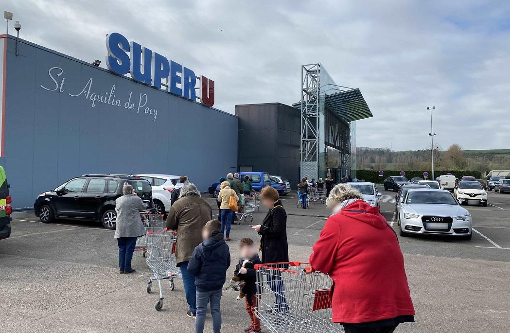 La peur de manquer : il  y avait encore beaucoup de monde à attendre son tour ce mardi matin, peu avant 12 heures, devant les magasins d'alimentation. Ici, à Pacy-sur-Eure - Photo © infoNormandie