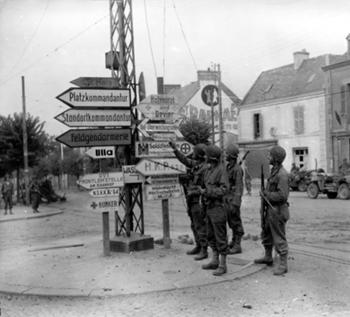 Bataille de Normandie été 1944 : Quatre GI's à un carrefour s'amusent à déchiffrer les panneaux indicateurs allemands qui désignent la direction des cantonnements, siège de l'état-major ou de la police militaire, abris-poste de secours, positions avancées...