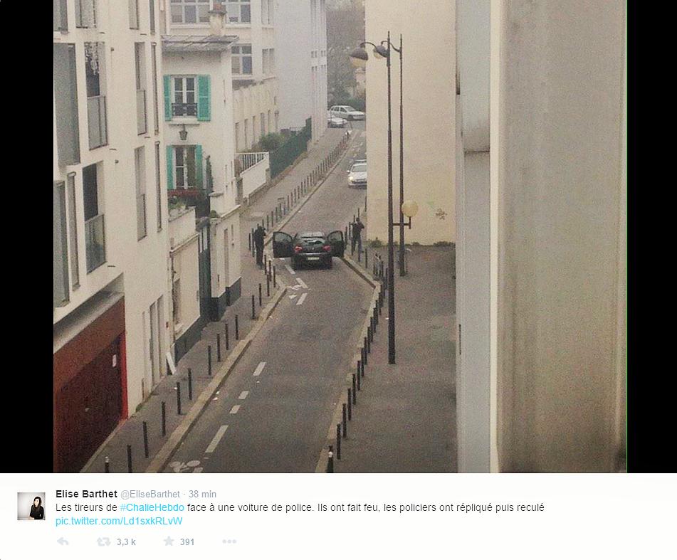Sur cette photo extraite du compte Twitter d'Elise Barthet / Le Monde, on aperçoit deux hommes encagoulés devant une voiture de police sur laquelle ils vont tirer avec des armes automatiques